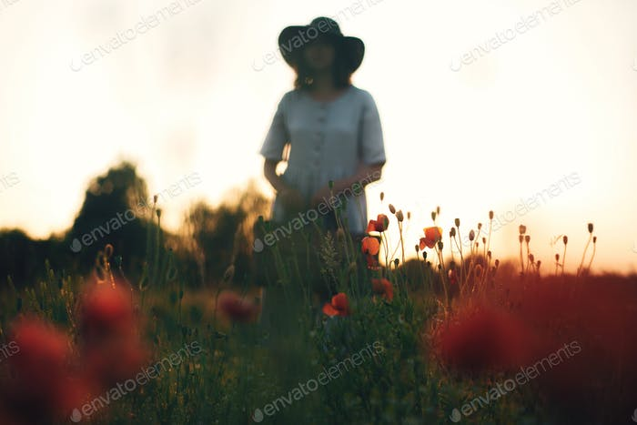 Focus on poppy flowers, blurred image of stylish girl in linen dress