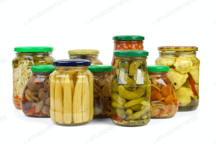 Glass jars with marinated vegetables and mushrooms