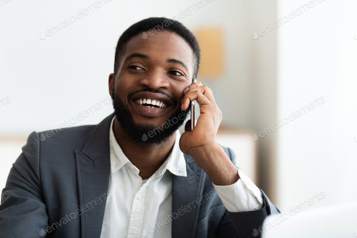 Happy black businessman talking on cellphone at office