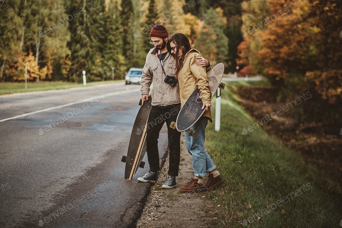 Nice couple are hitchhiking on the road
