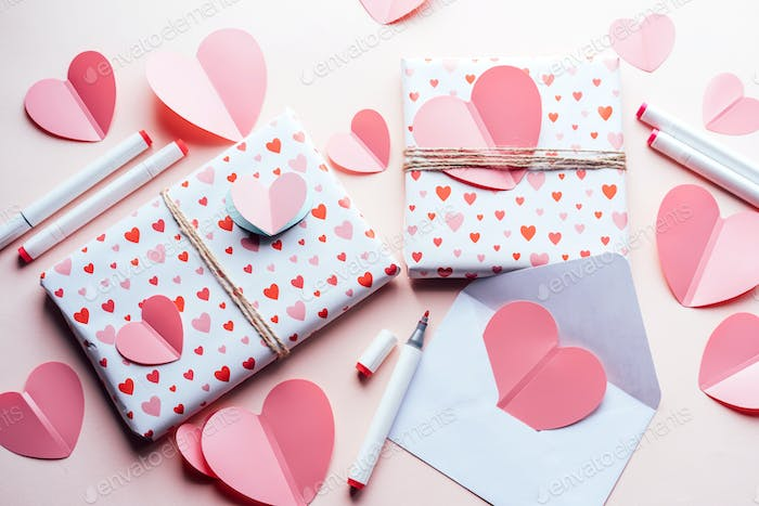 Top view of wrapped gifts and handmade hearts on a pink background.