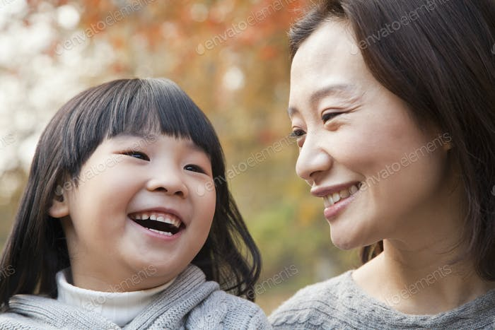 Close-up of Mother and Daughter laughing in the park, autumn, China