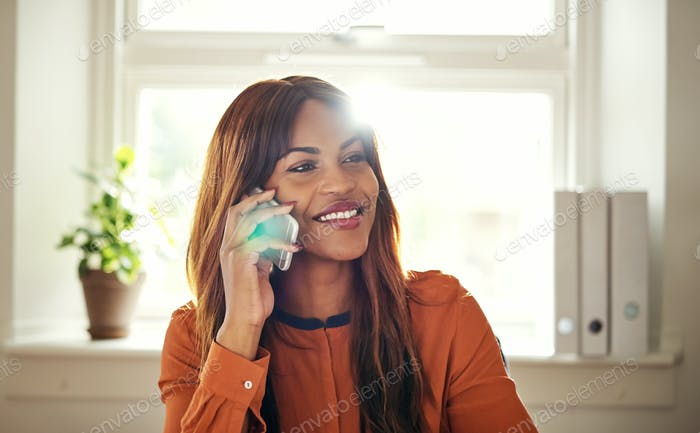 Smiling woman talking on a cellphone in her home office