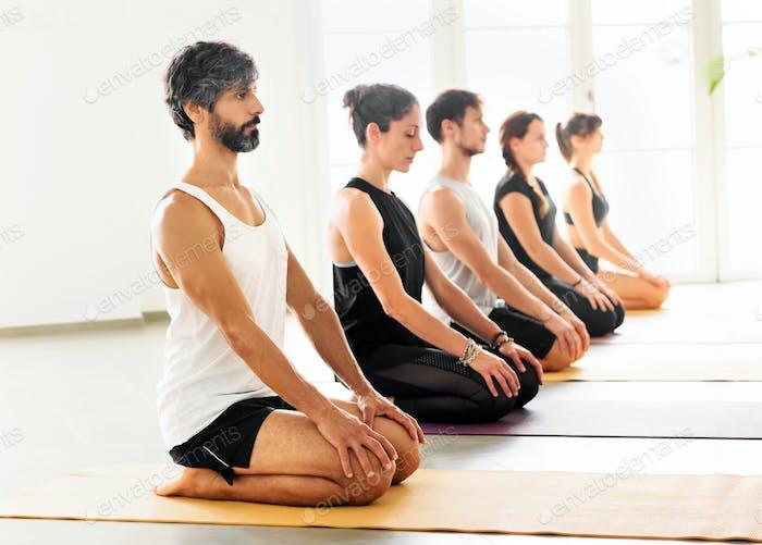 Reihe von Menschen, die in Virasana Pose meditieren