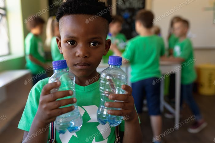 Schoolboy wearing a green t shirt with a white recycling logo on it and holding two plastic water bo