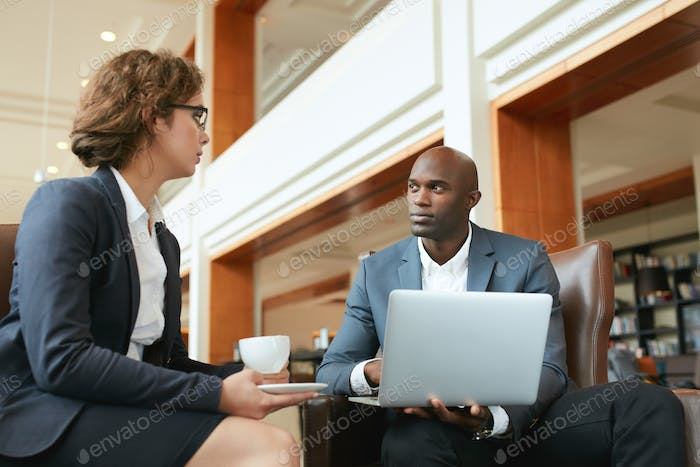 Two businesspeople having meeting in cafe with laptop