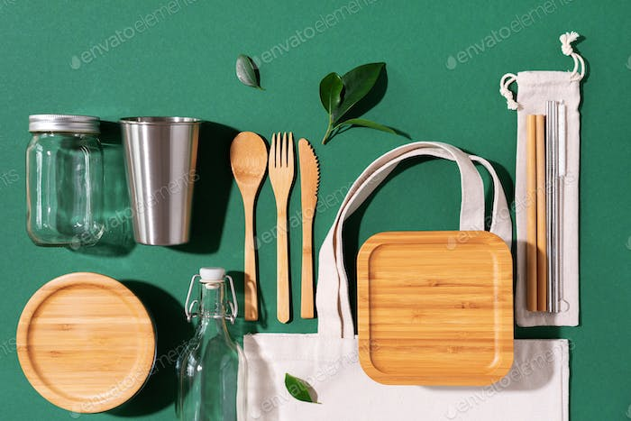 Cotton bags, glass jar, bottle, metal cup, straws for drinking, bamboo cutlery and boxes on green