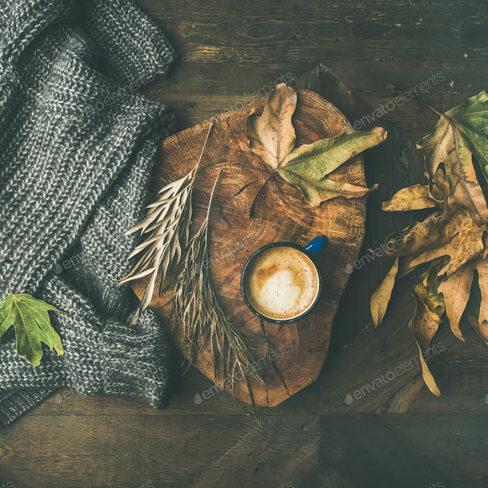 Autumn coffee concept with leaves and grey sweater, square crop