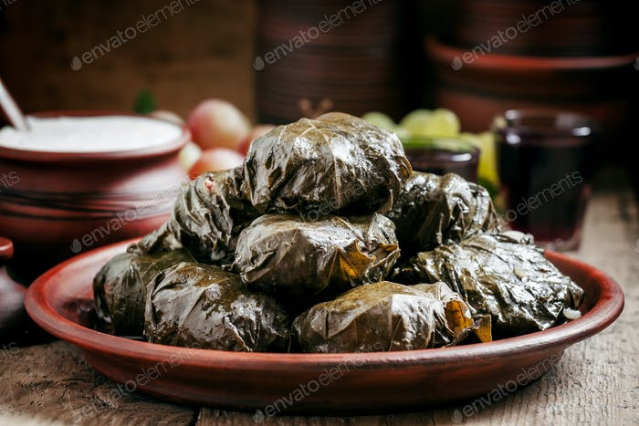 Traditional Greek dolma with meat in grape leaves, yogurt sauce, grapes and red wine