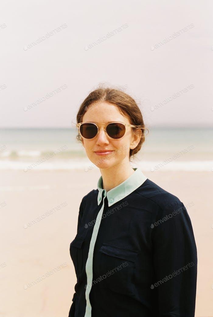 A woman wearing sunglasses on a beach.
