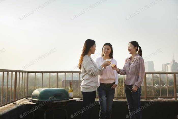 Junge Frauen Toast einander auf dem Dach bei Sonnenuntergang