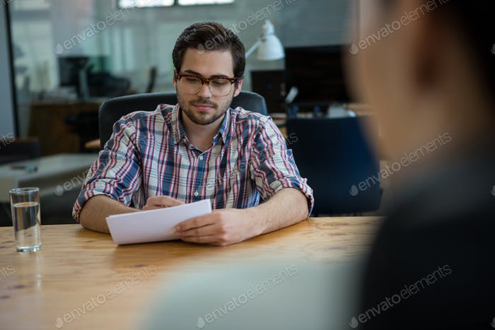 Business executive conducting job interview with woman
