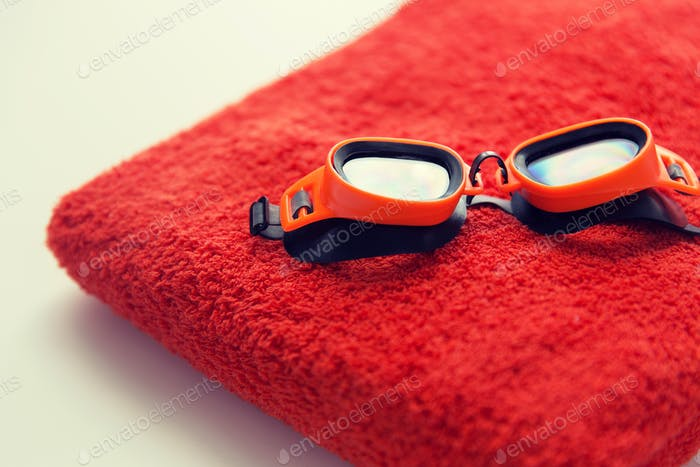 close up of swimming goggles and towel