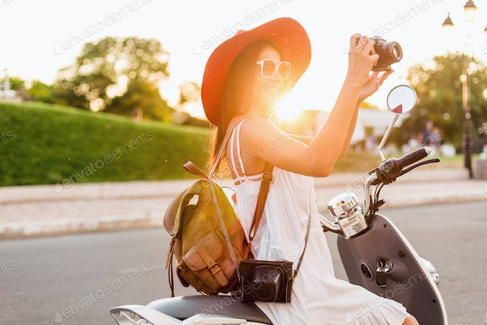 attractive woman riding on motorbike in street
