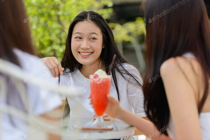 Three happy young Asian women as friends talking together at the coffee shop outdoors