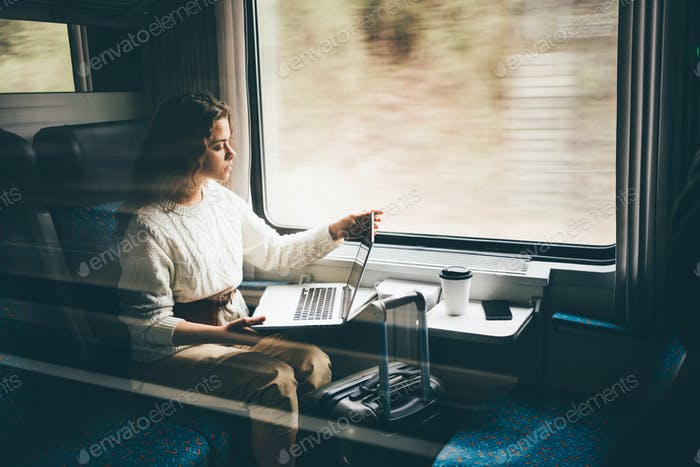 Freelancer girl working with laptop in the train.