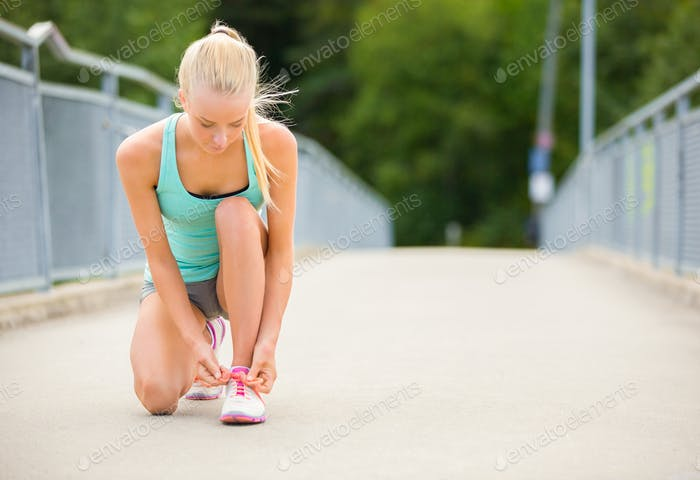 Young woman runner tying shoelaces on bridge