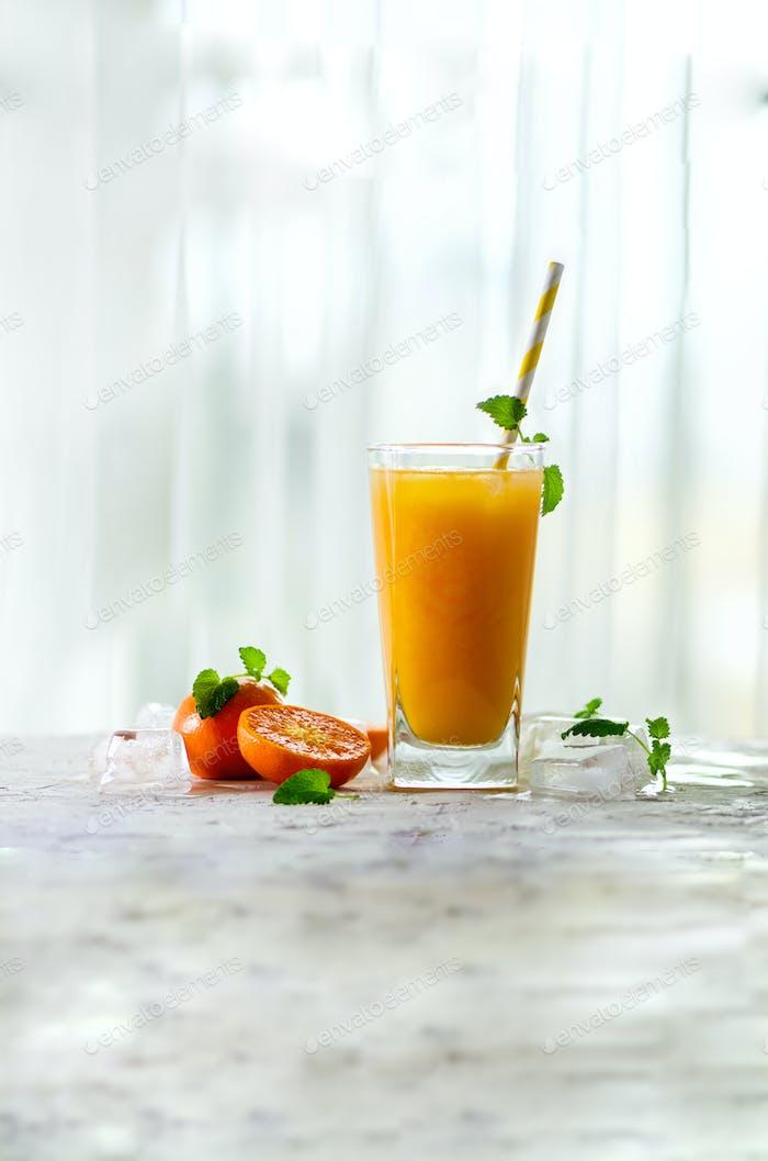 Frischer Orangensaft, Minze und Eis auf weißem Hintergrund, Draufsicht, Kopierraum. Sommercocktail, trinken