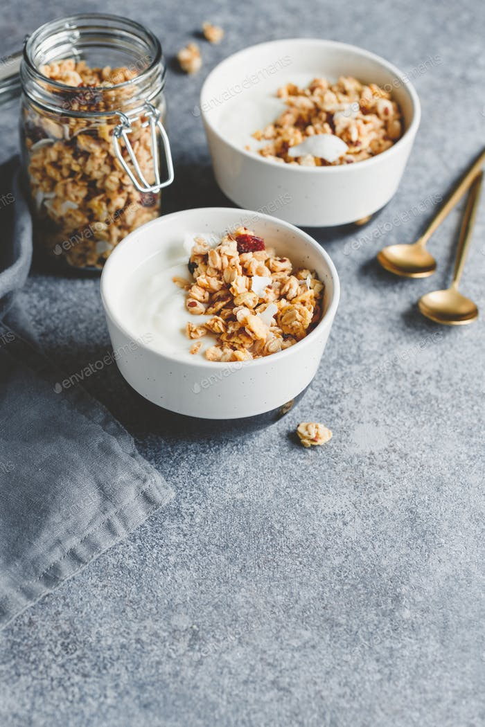 Breakfast bowl with organic granola, nuts, coconut chips and greek yoghurt.