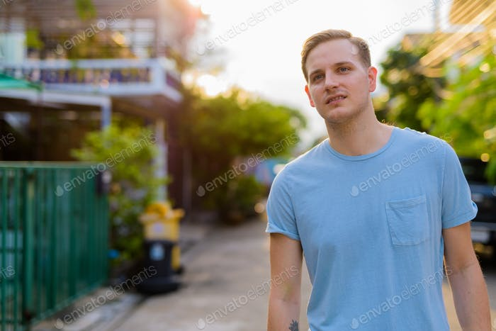 Young handsome man with blond hair in the streets outdoors