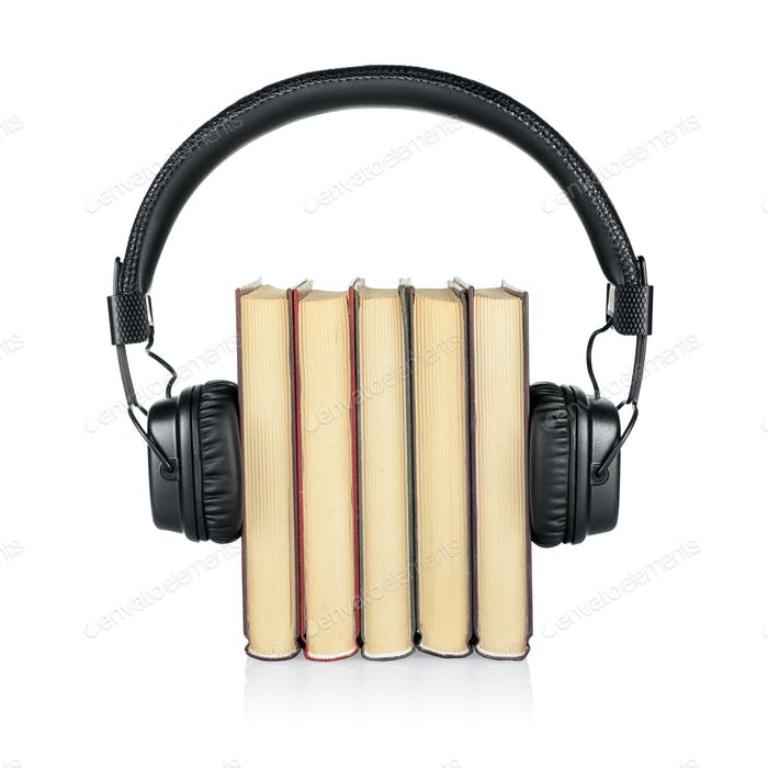 Audiobook concept. Stack of books and headphones isolated