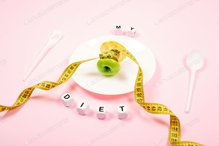 Apple core with measuring tape in place of the waist on a white plate with text MY DIET on pink
