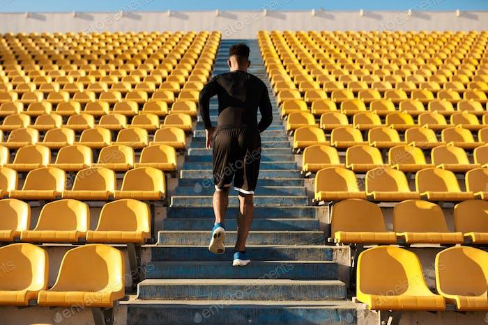 Rückansicht von jungen starken Afroamerikaner Sportler läuft unter leeren Stadionsitzen