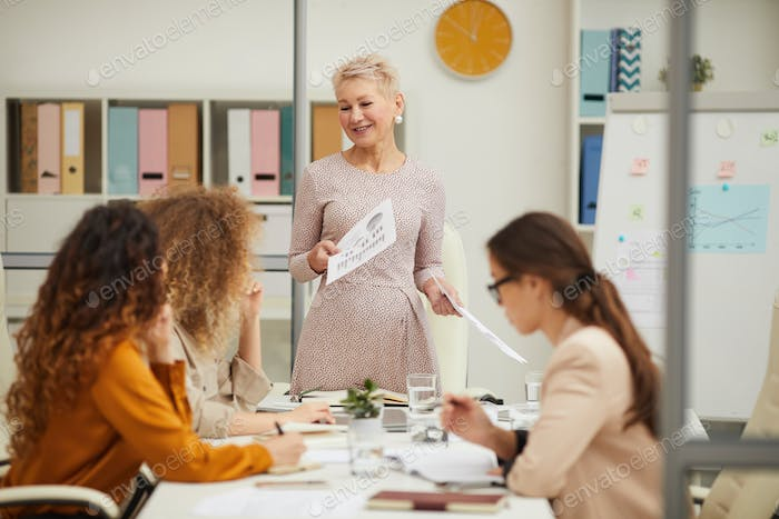 Mature Woman Holding Presentation In Office