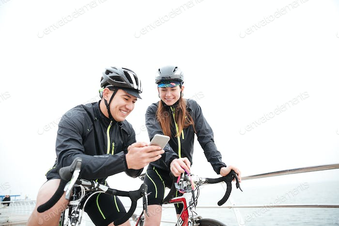 Smiling couple on bicycles resting and using smartphone