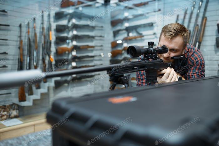 Man aims with sniper rifle in gun shop