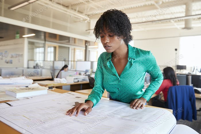 Black female architect studying plans in open plan office