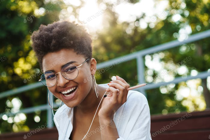 African woman sitting outdoors in park while listening music