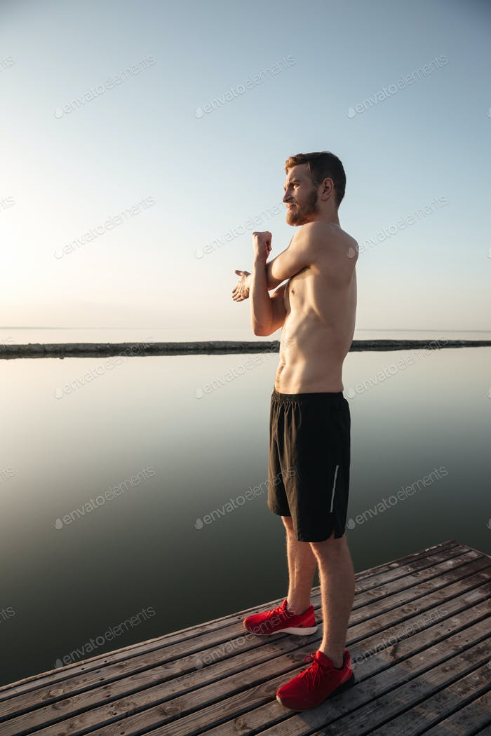 Portrait of a young shirtless sportsman warming up before jogging