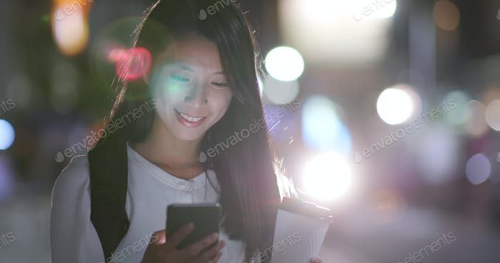 Woman use of mobile phone in the city of Taipei at night with holding coffee paper cup