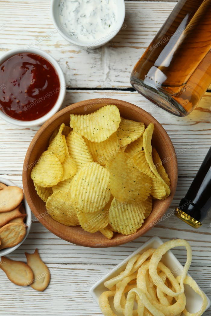 Different snacks, beer and sauces on white wooden background