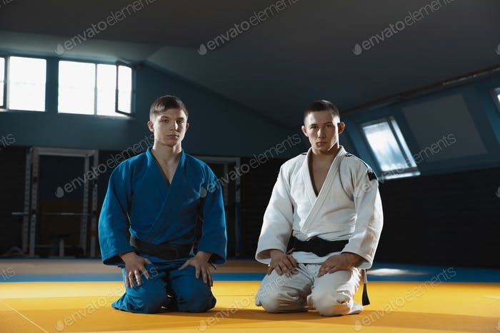 Two young judo fighters in kimono posing comfident in the gym, strong and healthy