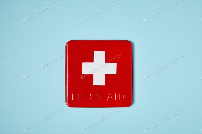 top view of red first aid kit box on blue surface