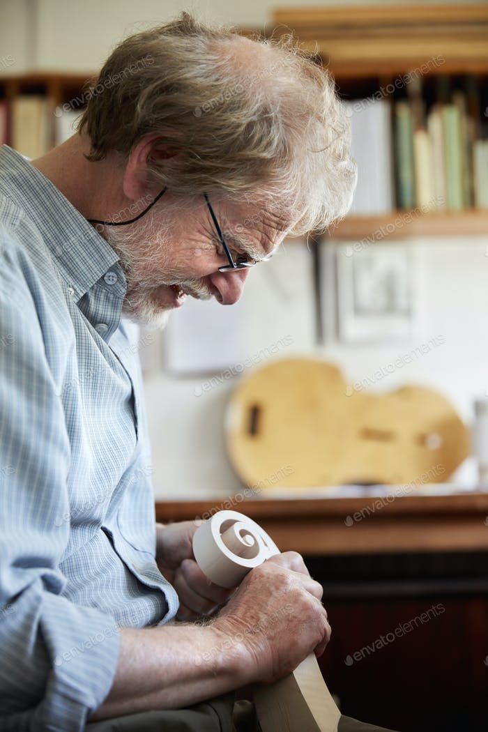 A violin maker using hand tools to smooth and finish a new wooden vioin headstock, curled scroll of