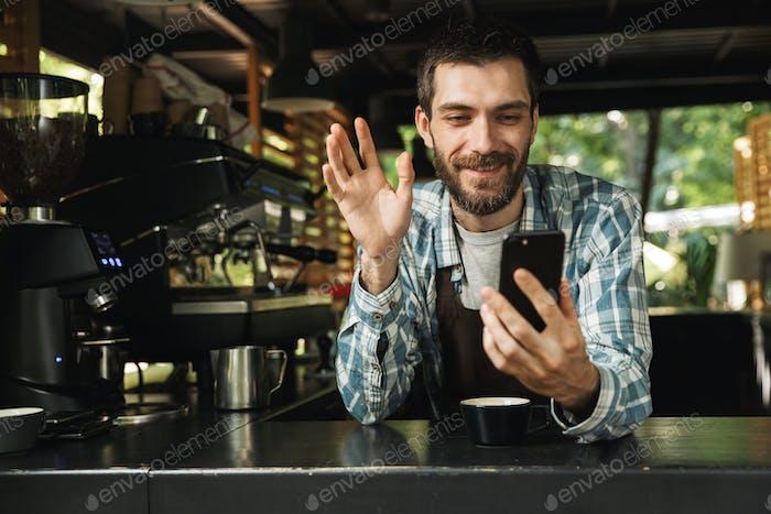 Foto von glücklicher Barista Kerl lächelnd während der Verwendung von Smartphone in caf