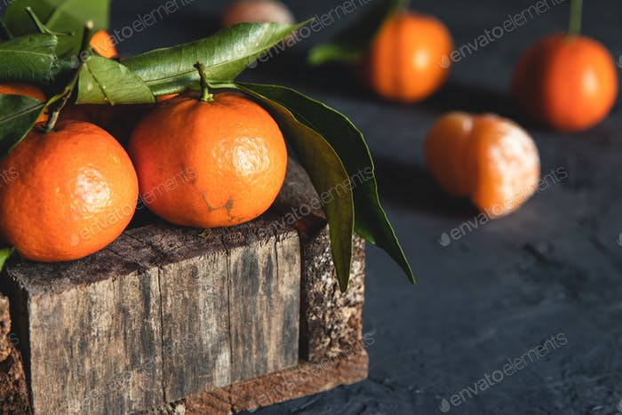 Box with tasty juicy tangerines in wood box on dark background with copy space