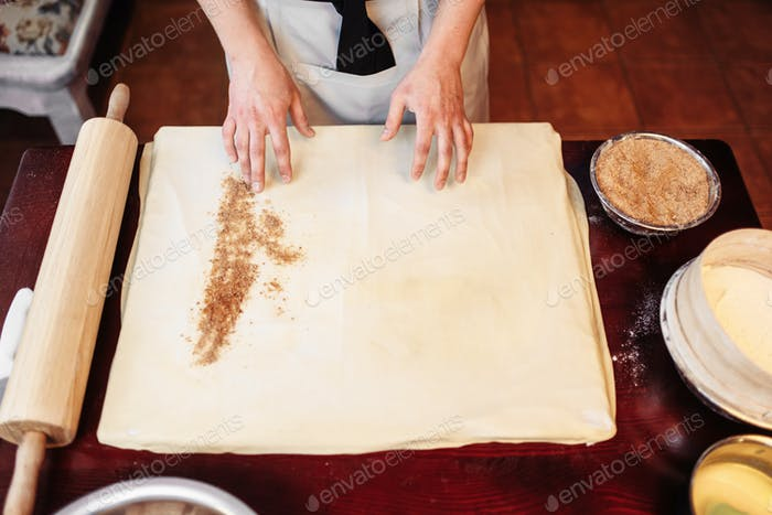 Male chef sprinkle the dough with cinnamon