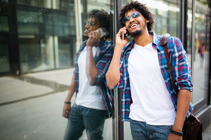 Close up portrait of laughing black young man talking on mobile phone and looking away