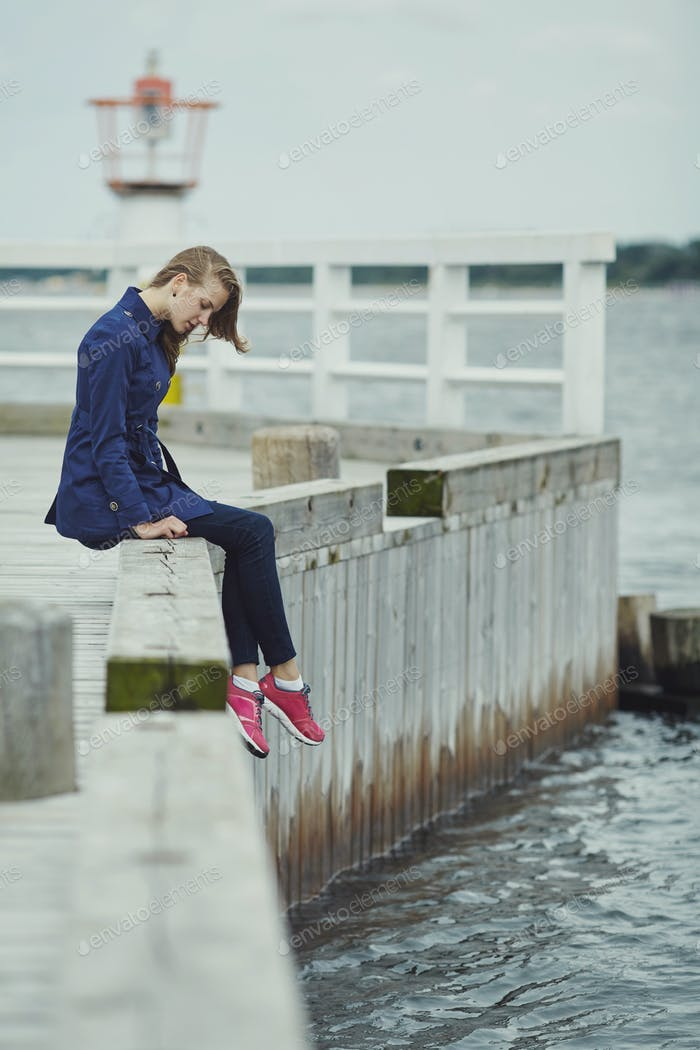 Beautiful blond girl sits on pier