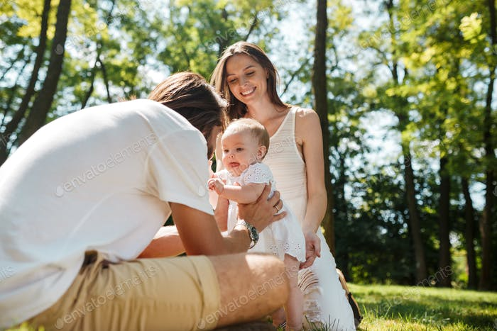 Happy beautiful parents dressed in the white casual clothes spending sunny day in the park with