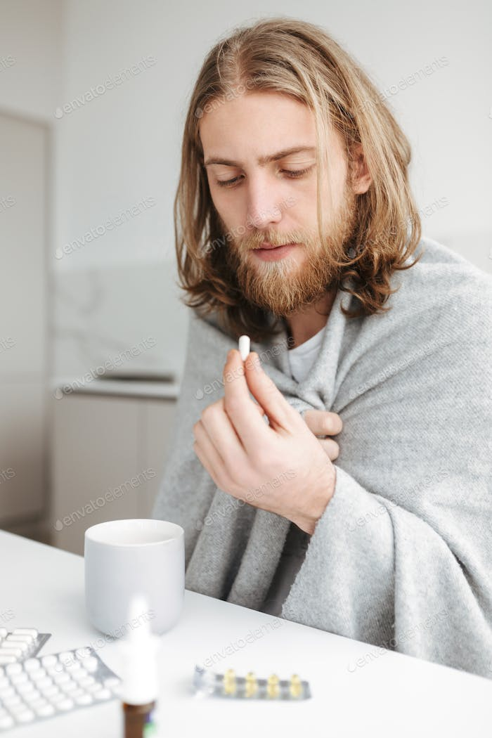 Young ill man sitting with mug and thoughtfully looking on pill in hand in kitchen at home