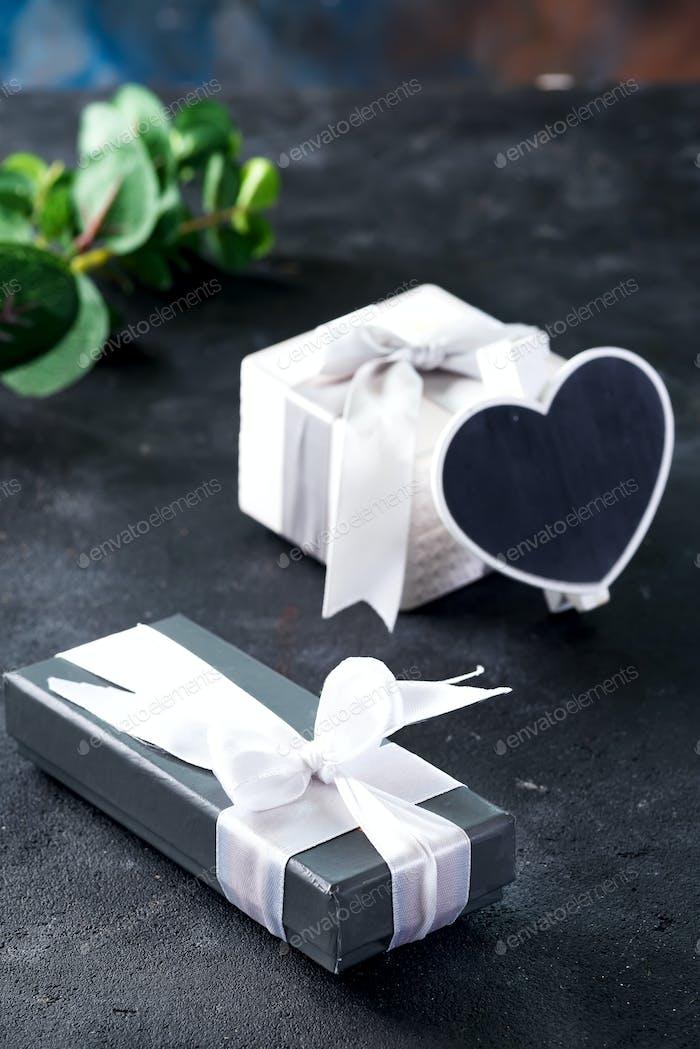 Geschenkboxen und Kreidetafel in Herzform mit grünem Pflanzenzweig auf dunklem Steinhintergrund