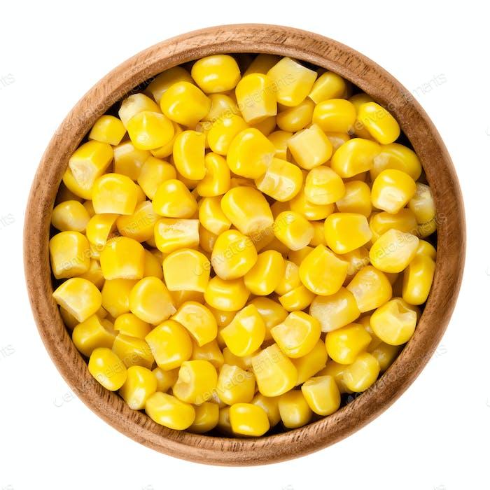 Sweet corn kernels in wooden bowl over white