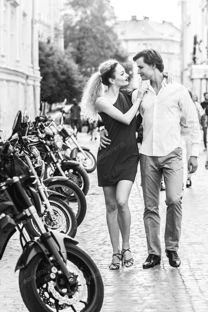 Glückliches Paar in der Liebe zu Fuß auf geparkten Motorrädern