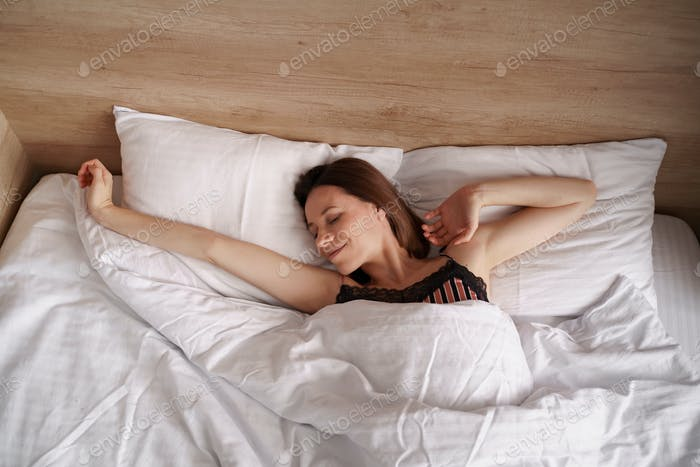 Caucasian Woman stretching in bed after wake up