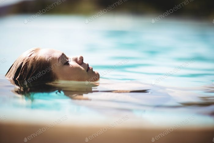 Peaceful blonde floating in the pool with eyes closed
